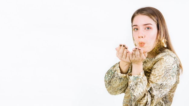Young woman blowing sparkles