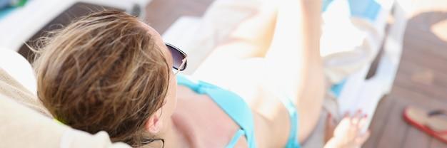 Young woman in blue bikini lies on sun lounger