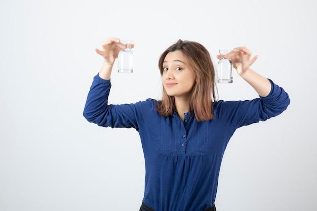 Giovane donna in camicetta blu che mostra un bicchiere d'acqua.