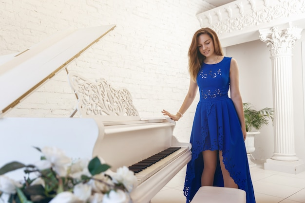 Young woman in a blue dress is standing near a white piano and look down
