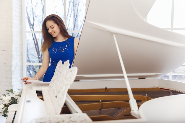 Young woman in a blue dress is standing near a white piano with notes in her hands