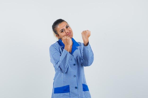 Giovane donna in camicia del pigiama a quadretti blu che stringe i pugni e sembra carina, vista frontale.