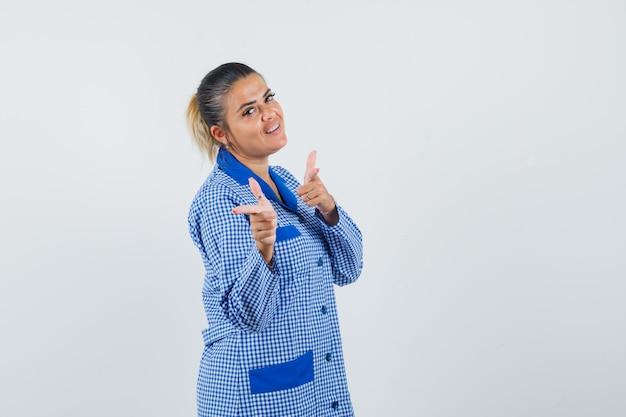 Giovane donna in camicia del pigiama a quadretti blu che punta con il dito indice e sembra carina, vista frontale.