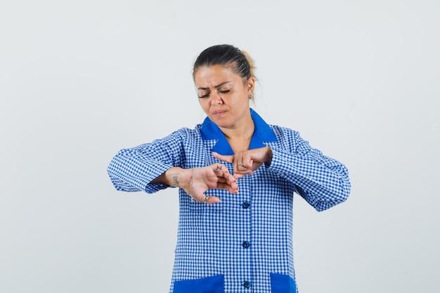 Giovane donna in camicia del pigiama a quadretti blu fingendo di guardare l'orologio e guardando concentrato, vista frontale.