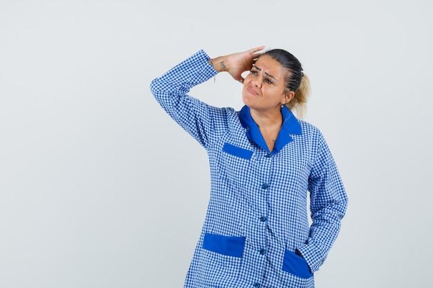 Giovane donna in camicia del pigiama a quadretti blu mettendo la mano sulla testa e guardando infastidito, vista frontale.
