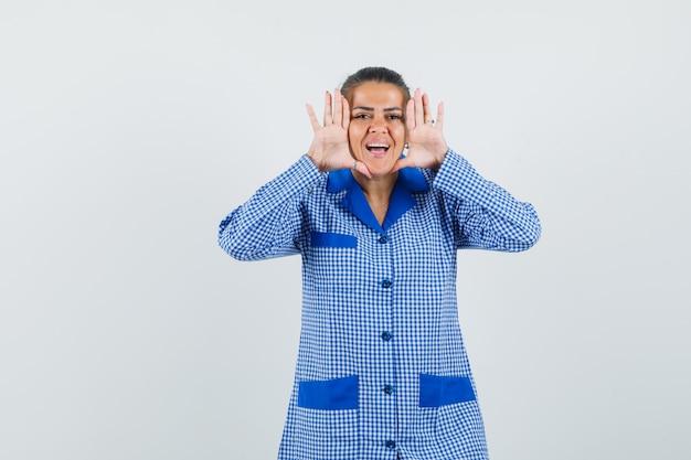 Giovane donna in camicia del pigiama a quadretti blu mettendo la mano vicino al viso, cercando di chiamare qualcuno e guardando felice, vista frontale.