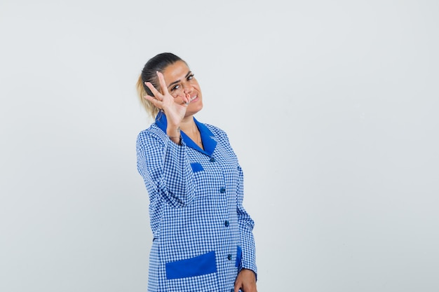 Young woman in blue gingham pajama shirt showing ok sign and looking pretty , front view.