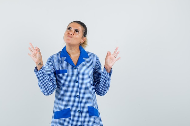 Young woman in blue gingham pajama shirt showing ok signs with both hands and looking pretty , front view.