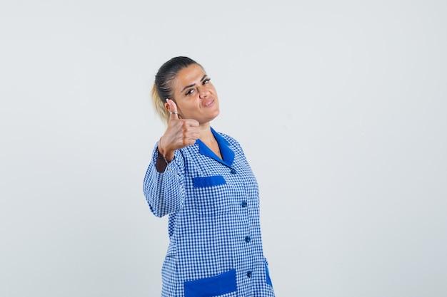 Giovane donna in camicia del pigiama a quadretti blu che mostra il pollice in su e sembra carina, vista frontale.