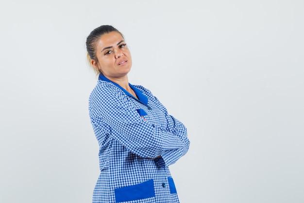 Giovane donna in camicia pigiama a quadretti blu in piedi con le braccia incrociate e guardando sopra la spalla e guardando piuttosto, vista frontale.