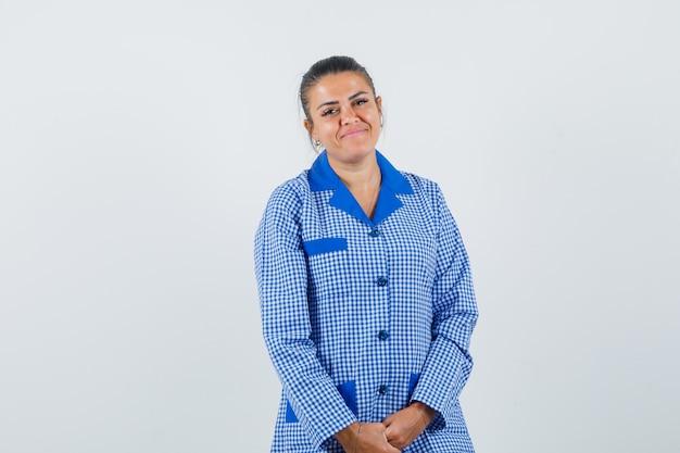 Giovane donna in camicia pigiama a quadretti blu in piedi dritto e in posa e sembra carina, vista frontale.