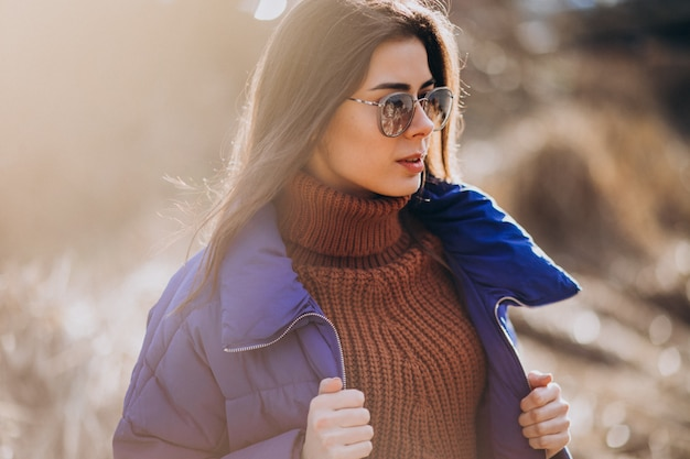 Young woman in blue jacket outside in park
