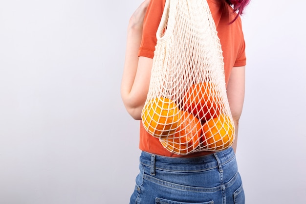 Young woman in blue jeans and orange t-shirt is on holds string bag with various citrus on grey background.