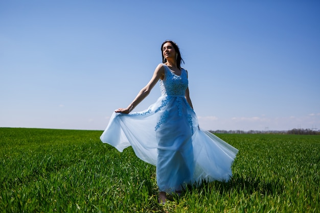Young woman in a blue long dress on a background of green field. fashion portrait of a beautiful girl with a smile on her face