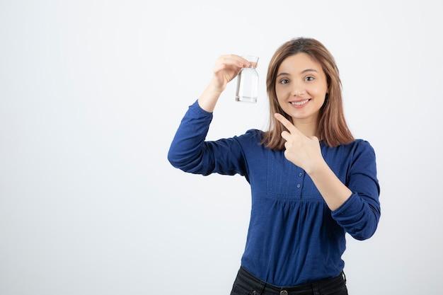 Giovane donna in blu che punta all'acqua in mano sul muro bianco.