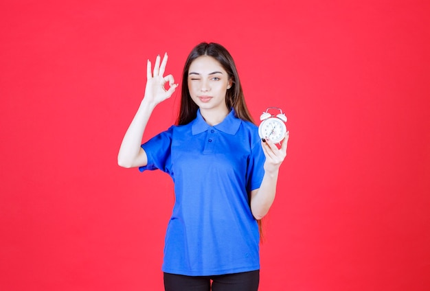 Young woman in blue shirt holding an alarm clock and showing positive hand sign