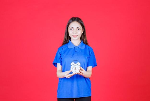 Giovane donna in camicia blu con in mano una sveglia
