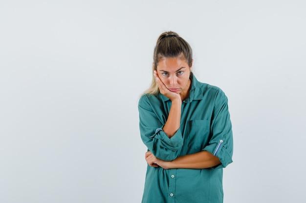 Giovane donna in camicia blu che guarda l'obbiettivo mentre si appoggia al suo gomito e sembra annoiato