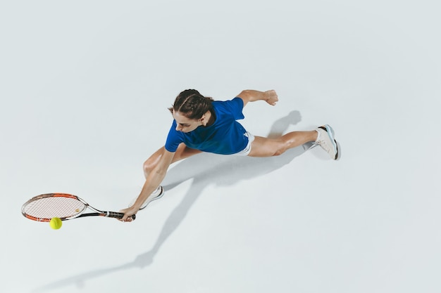 Young woman in blue shirt playing tennis. indoor studio shot isolated on white. top view.