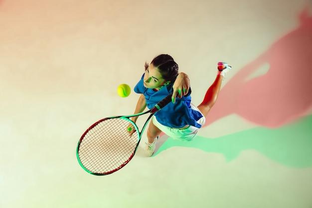 Giovane donna in camicia blu giocando a tennis. colpisce la palla con una racchetta. tiro in interni con luce mista. gioventù, flessibilità, potenza ed energia. vista dall'alto.
