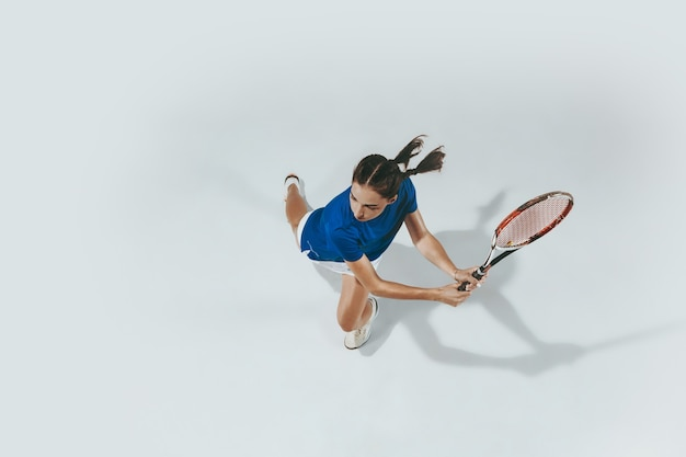 Young woman in blue shirt playing tennis. she hits the ball with a racket. top view