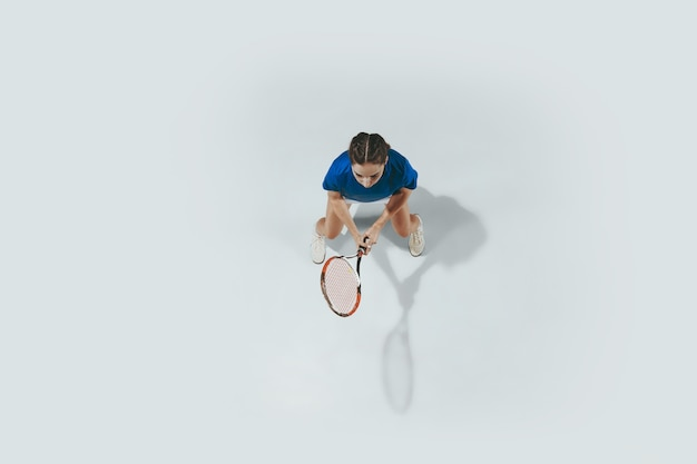 Young woman in blue shirt playing tennis. she hits the ball with a racket.