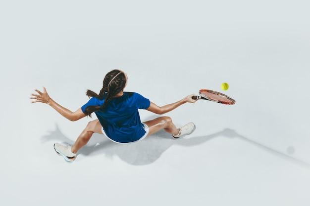 Giovane donna in camicia blu, giocare a tennis. vista dall'alto.