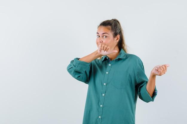 Giovane donna in camicia blu che indica indietro e che osserva attento