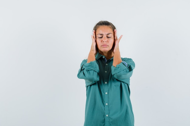 Young woman in blue shirt rubbing her temple and looking painful