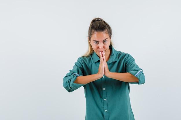 Giovane donna in camicia blu che mostra il gesto di namaste e che sembra concentrata