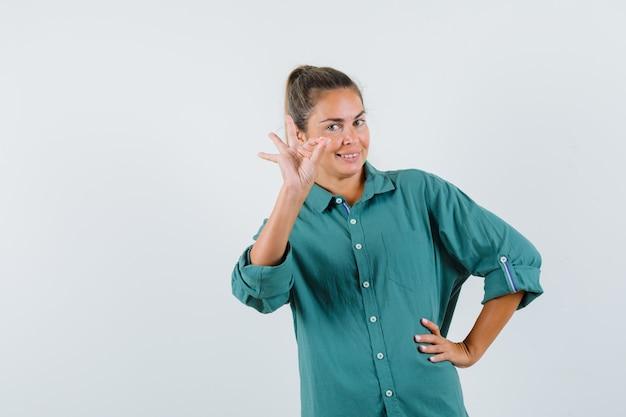 Giovane donna in camicia blu che mostra gesto giusto e che sembra contenta