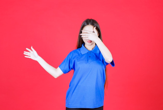 Young woman in blue shirt standing on red wall and pointing at someone around
