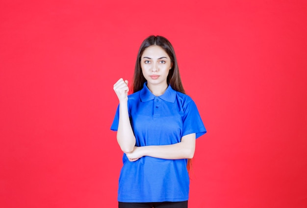 Young woman in blue shirt standing on red wall and showing positive hand sign