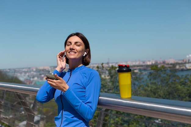 Young woman in blue sport wear on bridge at hot sunny morning with wireless headphones and mobile phone, resting listen to music