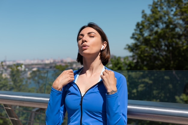 Young woman in blue sport wear on bridge at hot sunny morning with wireless headphones resting wave herself with hands, tired after workout jogging