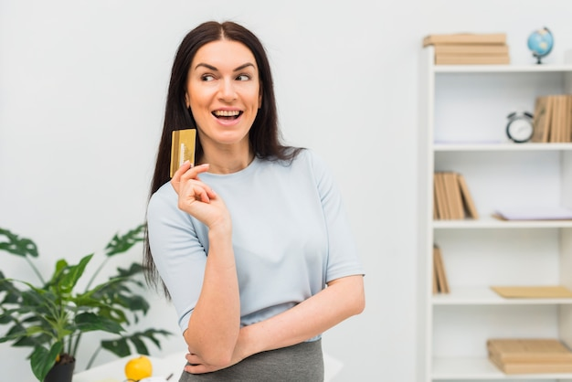 Young woman in blue standing with credit card in office