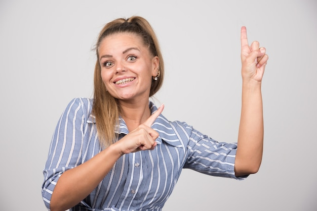 Young woman in blue sweater pointing at something.