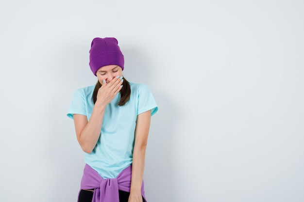 Young woman in blue t-shirt, purple beanie covering mouth with hand, laughing and looking jolly , front view.