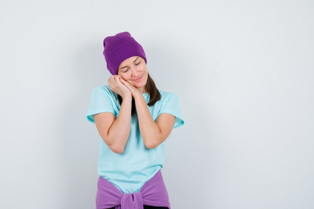 Young woman in blue t-shirt, purple beanie leaning cheek on palms as pillow and looking sleepy , front view.