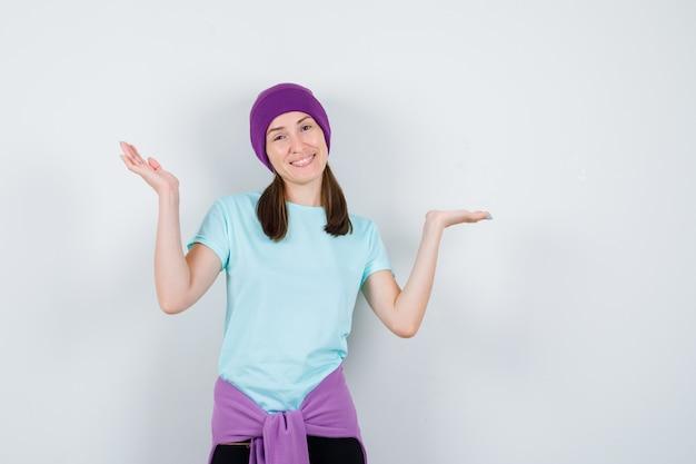 Giovane donna in maglietta blu, berretto viola che allarga le mani con gioia e sembra allegra, vista frontale.