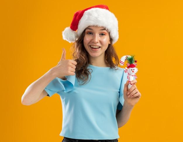 Giovane donna nella parte superiore blu e nel cappello della santa che tiene il bastoncino di zucchero di natale che sembra sorridere allegramente mostrando i pollici in su