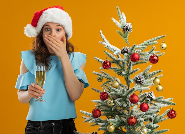 Young woman in blue top and santa hat  holding glass of champagne looking at camera being shocked covering mouth with hand standing next to a christmas tree over orange background
