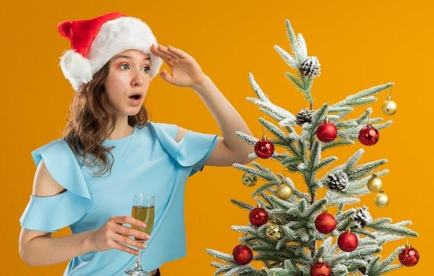 Giovane donna nella parte superiore blu e santa hat tenendo un bicchiere di champagne guardando lontano con la mano sulla testa di essere sorpreso in piedi accanto a un albero di natale su sfondo arancione