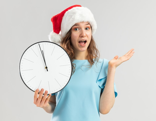 Young woman in blue top and santa hat holding wall clock looking surprised and happy with arm raised