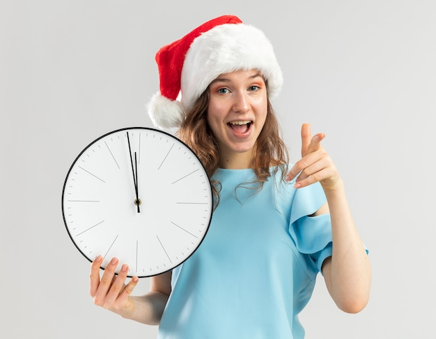 Young woman in blue top and santa hat holding wall clock pointing with index finger happy and positive
