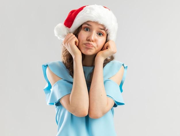 Giovane donna in cappello blu e in alto della santa che sembra confuso rendendo la bocca ironica con espressione delusa