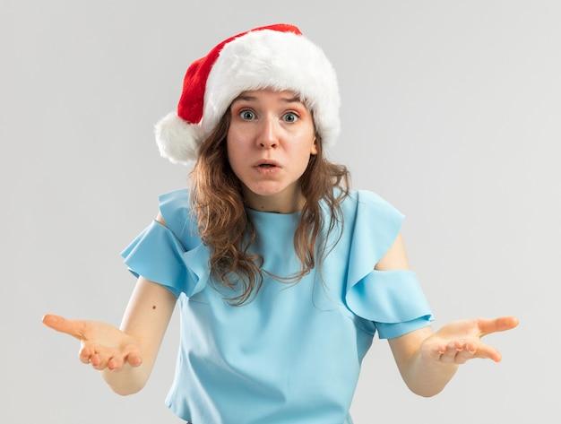 Giovane donna in cappello blu e cappello della santa che sembra confusa e molto ansiosa alzando le mani in indignazione e dispiacere