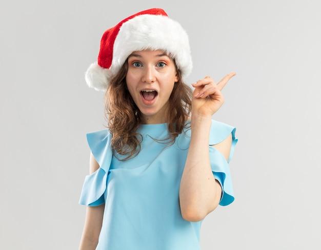 Giovane donna in cappello blu e santa che sembra sorpresa con il sorriso sul viso intelligente che ha una nuova grande idea che mostra il dito indice