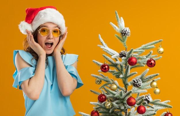 Giovane donna in top blu e cappello da babbo natale che indossa occhiali gialli stupita e sorpresa in piedi accanto a un albero di natale su un muro arancione