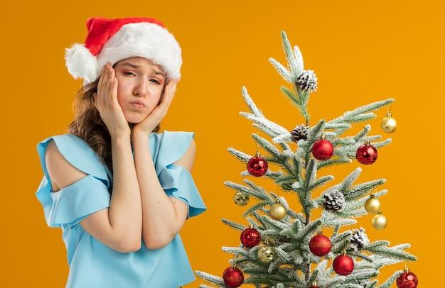 Giovane donna in top blu e cappello da babbo natale con gli occhiali gialli annoiata a soffiare le guance in piedi accanto a un albero di natale su un muro arancione